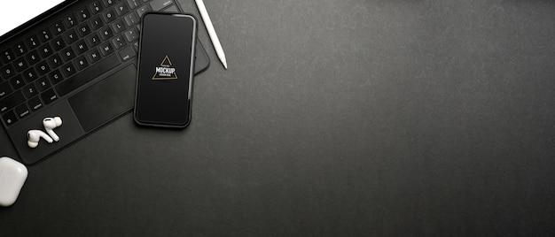 Donkere creatieve platliggende werkruimte met smartphonemodel en accessoires, bovenaanzicht
