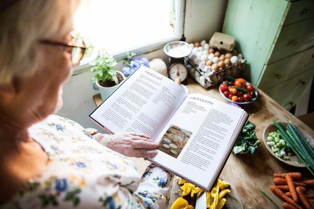 Donna anziana felice che legge un libro di cucina