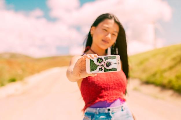 Donna asiatica che presenta il modello di smartphone in natura