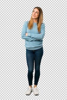 Donna bionda con la camicia blu che osserva in su mentre sorridendo