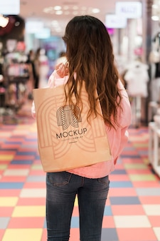 Donna che cammina nel centro commerciale con la borsa della spesa da dietro