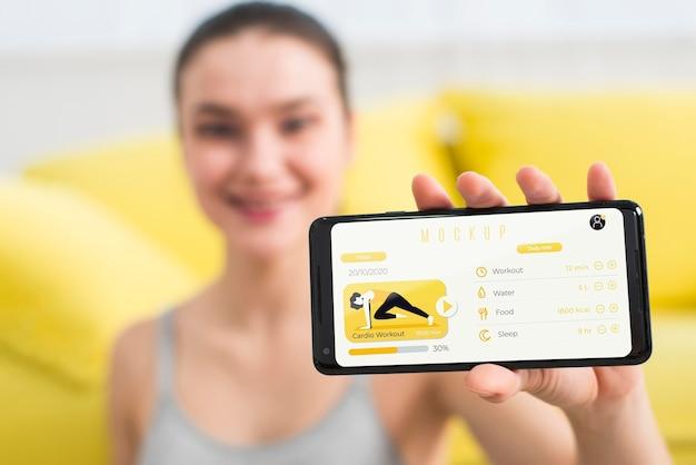 Donna che mostra un esercizio di fitness sul telefono cellulare