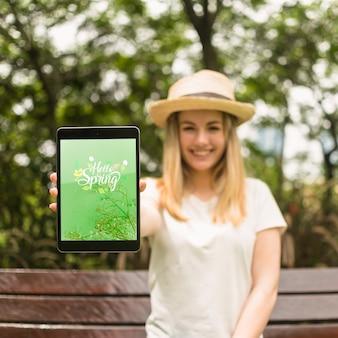Donna che presenta il modello di tablet in natura
