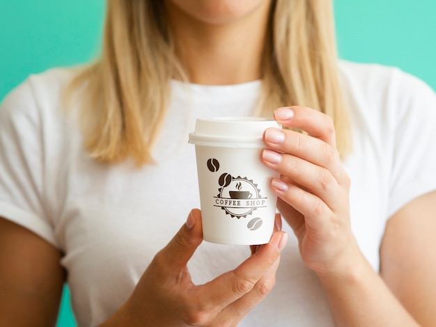 Donna che sostiene una tazza di carta del caffè