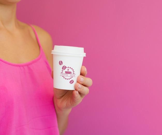 Donna che tiene il modello della tazza di caffè di carta con lo spazio della copia