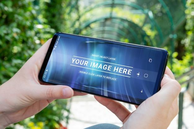 Donna che tiene smartphone moderno in un parco mockup