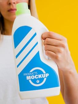 Donna che tiene un modello di bottiglia di pulizia