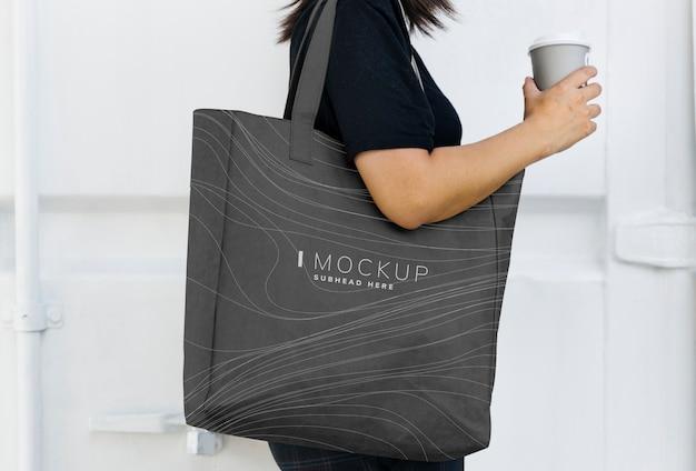 Donna che trasporta un mockup nero del sacchetto della spesa