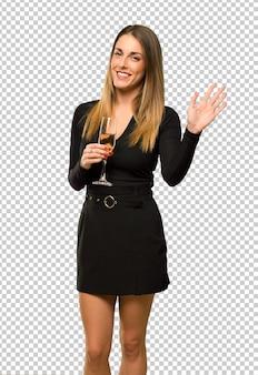 Donna con champagne che celebra il nuovo anno 2019 salutando con la mano con espressione felice