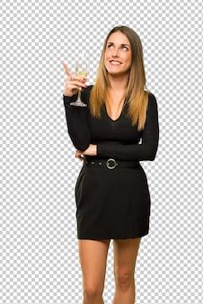 Donna con champagne festeggia il nuovo anno 2019 che punta con il dito una grande idea e guardando in alto