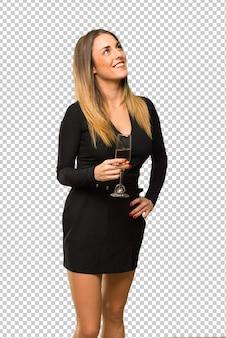Donna con champagne festeggia il nuovo anno 2019 in posa con le braccia in anca e ridendo