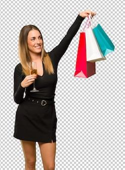 Donna con champagne festeggia il nuovo anno 2019 in possesso di un sacco di borse per la spesa