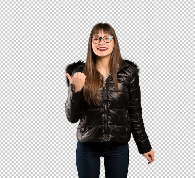 Donna con gli occhiali che punta al lato per presentare un prodotto