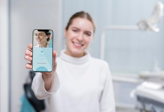 Donna del colpo medio che tiene uno smartphone