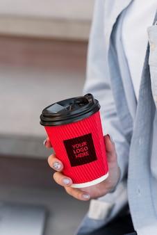 Donna del primo piano che tiene un modello della tazza di caffè
