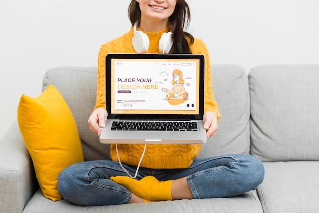 Donna del primo piano con le cuffie e il computer portatile