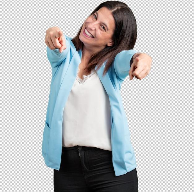 Donna di mezza età allegra e sorridente che punta verso la parte anteriore