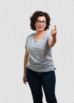 Donna di mezza età che mostra il numero uno, simbolo del conteggio, concetto di matematica, fiducioso e allegro