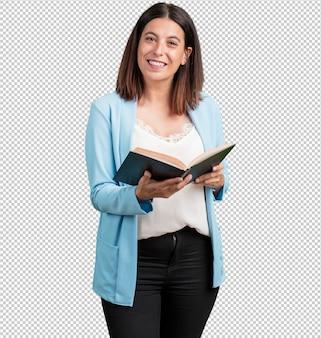 Donna di mezza età concentrata e sorridente, con in mano un libro di testo, studiando per superare un esame o leggere un libro interessante