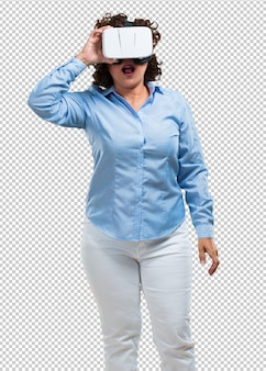 Donna di mezza età eccitata e divertita, giocando con gli occhiali per realtà virtuale.