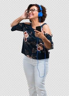Donna di mezza età felice e divertente, ascoltando musica, cuffie moderne, felice sentendo il suono e il ritmo