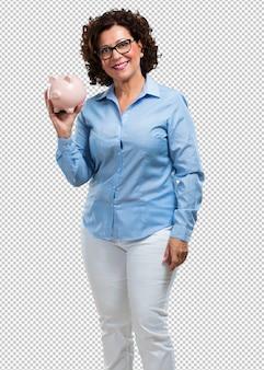 Donna di mezza età fiduciosa e allegra, con una banca di maialino e di essere tranquilla