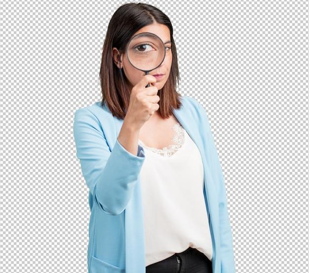 Donna di mezza età sorpresa e con gli occhi spalancati guardando attraverso una lente d'ingrandimento, studiando qualcosa, trovando prove