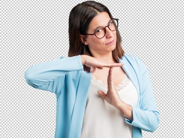 Donna di mezza età stanca e annoiata, facendo un gesto di timeout, ha bisogno di fermarsi a causa di stress da lavoro, il concetto di tempo
