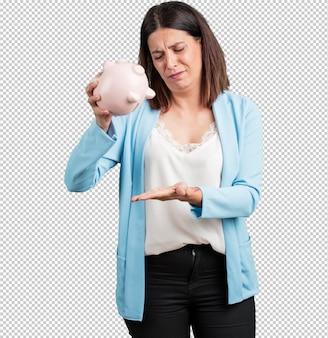 Donna di mezza età triste e delusa, con in mano una banca di maialini, senza soldi, cercando di tirar fuori qualcosa, volto di rabbia e angoscia, concetto di povertà