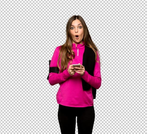 Donna giovane sportivo sorpreso e inviando un messaggio