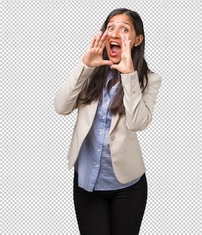 Donna indiana di giovani affari che grida felice, sorpresa da un'offerta o una promozione, spalancata, saltando e orgogliosa