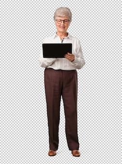 Donna senior dell'ente completo che sorride e sicura, tenendo una compressa, usando per navigare in internet e vedere i media sociali, concetto di comunicazione