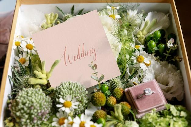 Doos gevuld met diverse bloemen en een trouwring