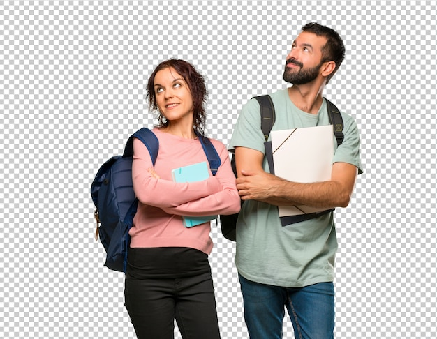 Dos estudiantes con mochilas y libros mirando hacia arriba mientras sonríe