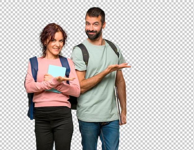 Dos estudiantes con mochilas y libros que presentan una idea mientras miran sonriendo hacia