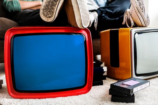 Dos hombres sentados junto a televisores retro