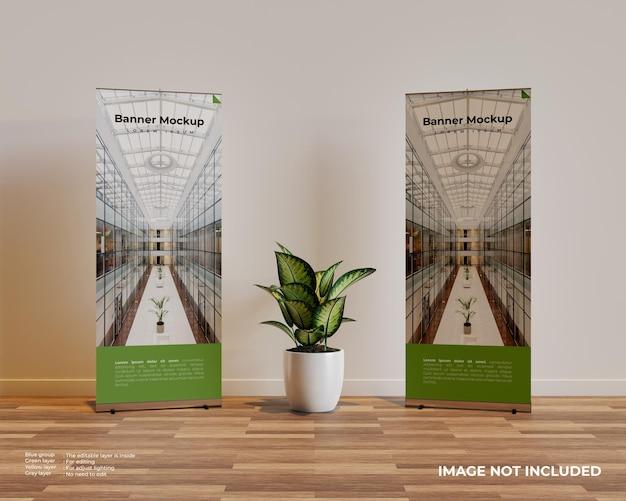 Dos maquetas de banner enrollable en escena interior con una planta en el medio