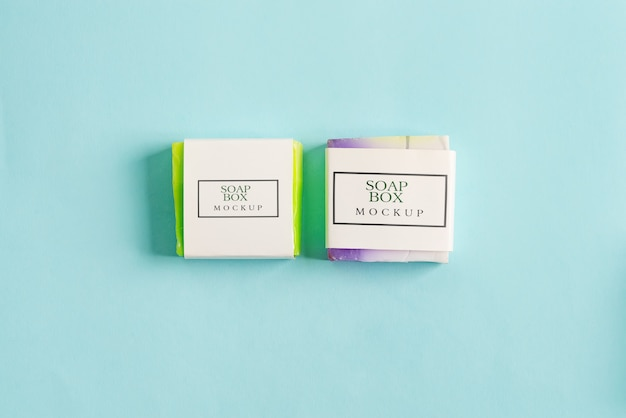 Dos paquetes de maquetas de caja de envoltura de jabón hecho a mano con barra de jabón colorido aislado sobre fondo azul.