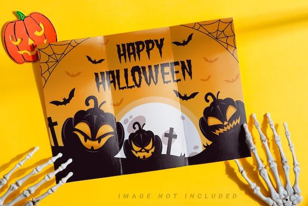 Driebladige papieren mock-up brochure in de handen van een skelet.