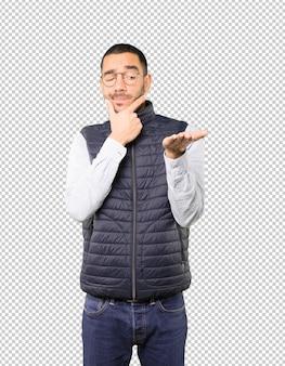 Dudoso joven sosteniendo algo con su mano