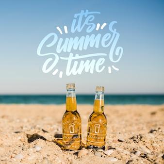 Due bottiglie sulla spiaggia con spazio di copia