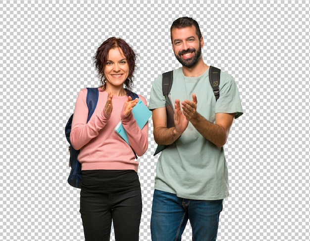 Due studenti con zaini e libri che applaudono dopo la presentazione in una conferenza