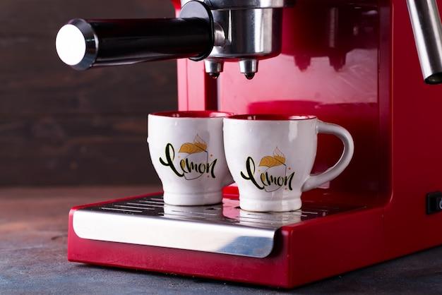 Due tazze di caffè nero mattina sulla macchina del caffè rosso mockup