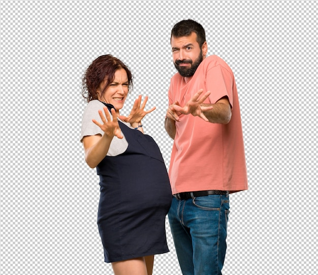 Echtpaar met zwangere vrouw is een beetje nerveus en bang uitrekkende handen aan de voorkant