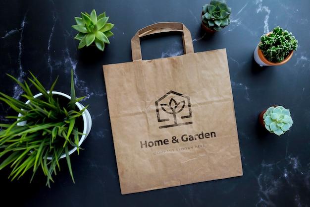 Eco kraft papieren zak met logo mockup op zwarte achtergrond en planten
