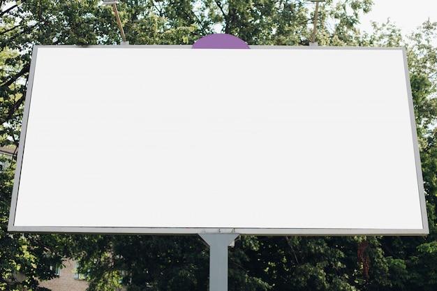 Een groot reclamebord met een reclamefoto erop in het park op straat