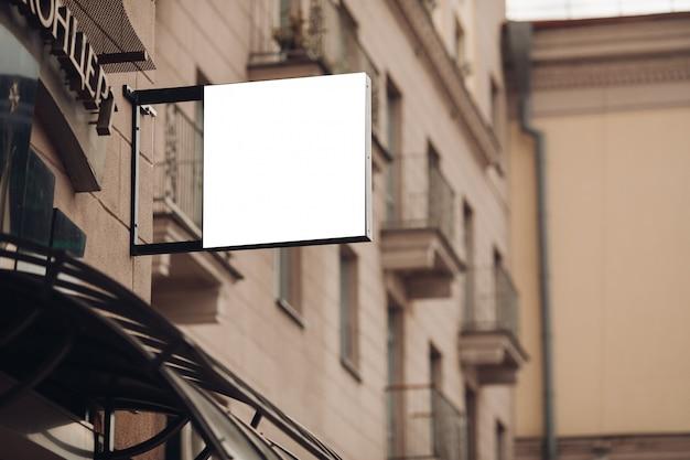 Een klein reclamebord, mockup op een gebouw in het stadscentrum met een café-advertentie