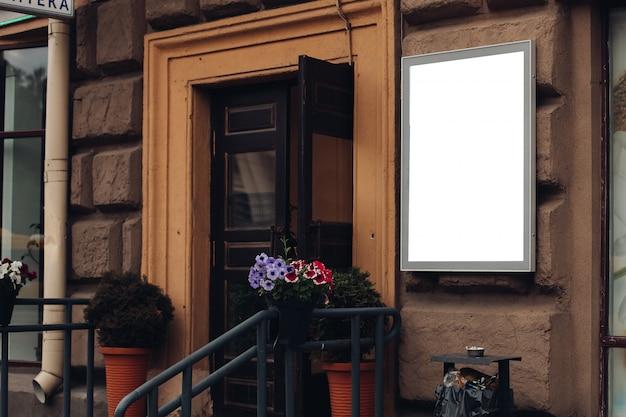 Een klein reclamebord, mockup op een gebouw in het stadscentrum met een winkelreclame
