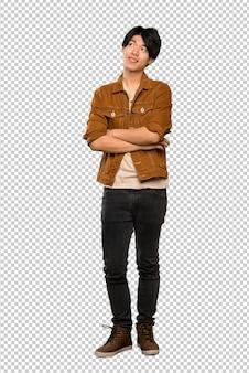 Een volledig lengteschot van een aziatische mens die met bruin jasje omhoog terwijl het glimlachen kijkt