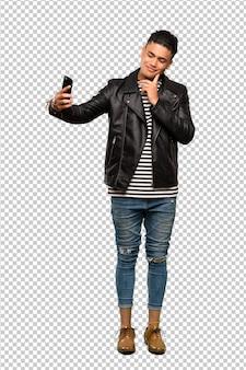 Een volledige lengte shot van een jonge man die een selfie